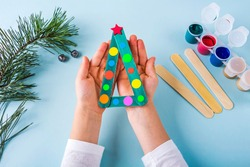 Concept of DIY and kid's creativity. Step by step instruction: how to make christmas tree made of ice cream sticks. Step 5 Child's holding  finished New year handmade craft tree.