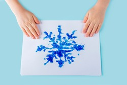 Concept of DIY and kid's creativity. Step by step instruction: how to make drawing of snowflake with glue and salt. Step 6 child's hands holds drawing with finished snowflake. Children Christmas craft