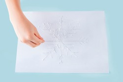 Concept of DIY and kid's creativity. Step by step instruction: how to make drawing of snowflake with glue and salt. Step 4 child's hands sprinkles salt on glue. Children Christmas and New year craft