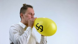 Concept of dollar as an air balloon. Young businessman in white shirt's blowing up yellow balloon with us dollar sign. Isolated on white background.