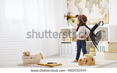 Stock Photo concept of  dreams and travels.  pilot aviator child with a toy airplane plays at home in his room