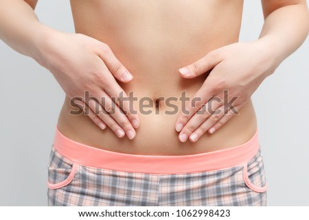 Concept of early term of pregnancy. Close up photo of woman's abdomen and belly button, she is touching her slim stomach with two hands. isolated on white background #1062998423