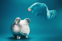 Concept of economic recession and money saving in the time of covid-19 pandemic. A hand inside surgical protective glove, holding one euro coin above piggy bank with face mask.