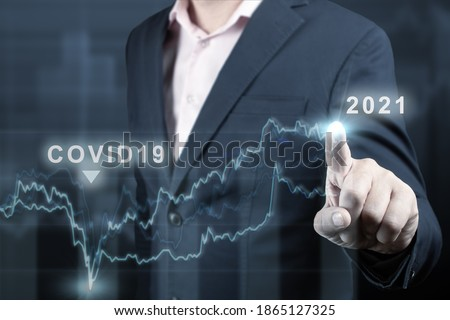 concept of economic recovery after the fall due to the covid 19 coronavirus pandemic. Double exposure of financial graph. Businessman pointing graph corporate future growth plan on dark blue Foto stock ©