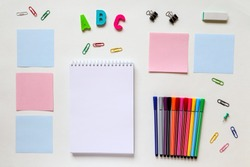 concept of education. on a white background are spread out notes and colored markers in the center a Notepad with a blank sheet for writing next to randomly scattered colored paper clips