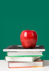 Concept of education. Red apple on top of a stack of schoolbooks and notebook against blackboard in classroom.
