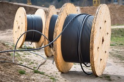 Concept of electricity supply for construction projects. Several wooden coils with power cable laid in trench.