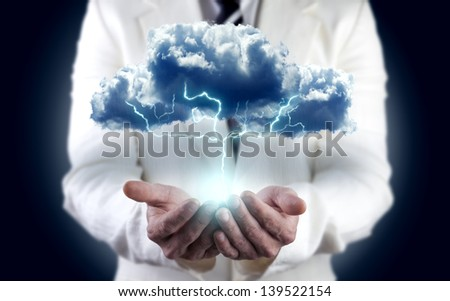 concept of energy and electricity.Environment . Businessman holding cloud with lightning