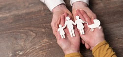 Concept of family insurance with paper family in hands
