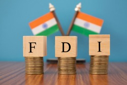 Concept of FDI or foreign Direct Investment on India in wooden block letters on stack of coins with Indian Flag as a background.