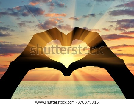 Concept of feelings and emotions. Silhouette of the heart of the gesture of hands on background of sea sunset
