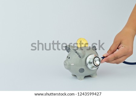 Concept of financial bitcoin diagnostics and cryptocurrency exchange rate forecasting. Funny piggy bank, bitcoin and stethoscope on gray background #1243599427