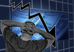 Concept of financial problems. Man holding his head while the markets plunge and his savings and wealth disappear on a blue graph pointing down background with dollar bills.