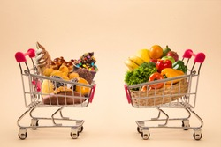 Concept of food and diet. Wafers, chocolate, ice cream and fruits and vegetables in shopping cart. Fast food addiction. Struggling with overweight and obesity. comparison between light food and fatten
