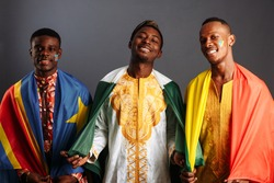 Concept of friendship between African countries: 3 American men in national clothes from different countries stay hug together with flags of Democratic Republic Congo, Republic of the Congo, Nigeria