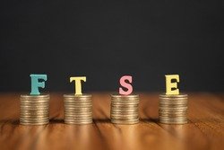 Concept of FTSE or Financial Times Stock Exchange showing with coins and letters on black background.