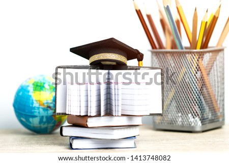 Concept of global business study abroad education. Graduation hat on models globe, books with pencils on wood white background. Congratulations to graduated, Studies lead to success. Back to School