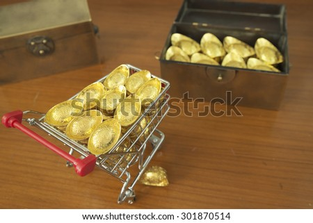 Concept of gold treasuring into treasure chest by pushcart with a gold drop on its\' side. The chinese words are crafted into gold with meaning of good fortune, best of luck, and good health.