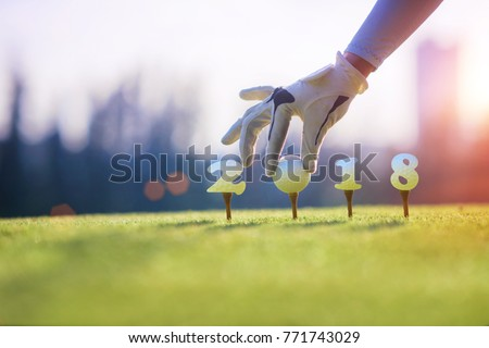 concept of golf ball invitation incomming year 2018, on the tee off prepare by hand of woman in the golf course