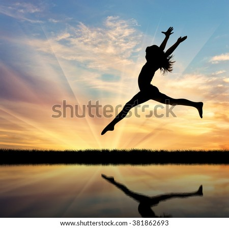 Concept of happiness and freedom. Silhouette of happy woman jumping at sunset and reflection in water #381862693