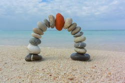 Concept of harmony and balance. Balance stones against the sea. Zen and red on top.