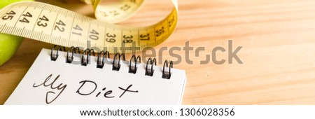Concept of healthy eating, dieting, losing weight and losing weight - close up diet paper plan, tape measure on wooden background