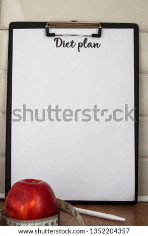 Concept of healthy eating, dieting, losing weight and losing weight - close up of a diet plan paper with red apple and measuring tape