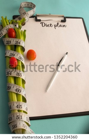 Concept of healthy eating, dieting, losing weight and losing weight - close up of a paper diet plan with celery and cherry tomatoes and a measuring tape