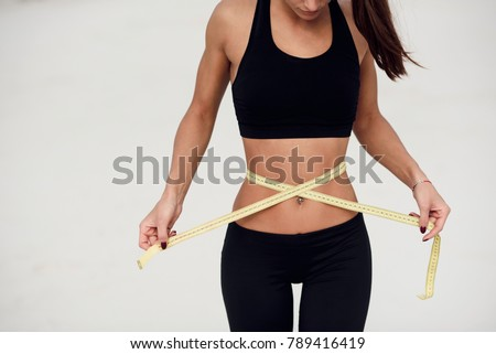 Concept of healthy eating. Young girl with perfect waist with a measuring tape in hands