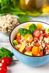 Concept of healthy food, clean eating, low calories delicious meal. Salad with quinoa and fresh vegetables with olive oil in blue bowl. Tomato, avocado, spinach. Close up wooden background banner