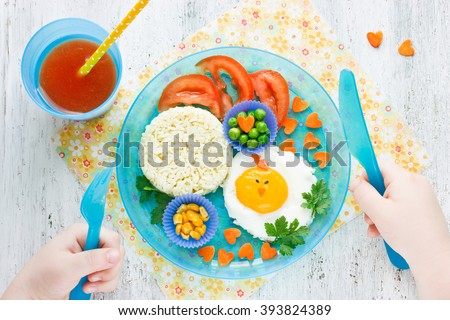 Concept of healthy food for child. Food art idea for kids breakfast egg and vegetable garnish tomato juice top view