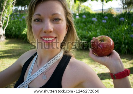 Concept of healthy nutrition  and active life for women after the age of 30, 40 or 50. Beautiful smiling slender woman with wrinkles but looking younger than her years with aa apple and waist meter.