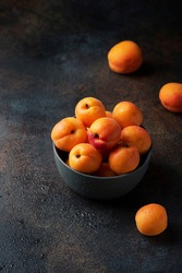 Concept of healthy vegan food with sweet apricots in a dark background, selective focus image