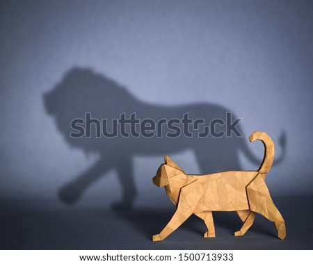 Concept of hidden potential. A paper figure of a cat that fills the shadow of a lion. 3D illustration