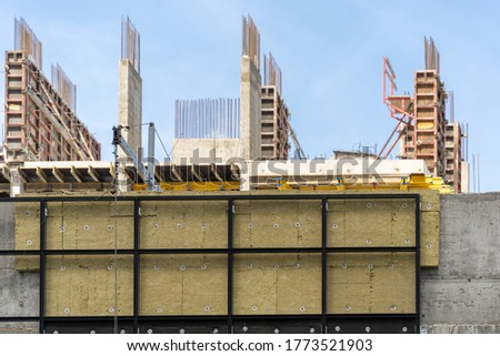 Concept of housing development project. Selective focus on building under construction with rock wool insulation on exterior and reinforcement formwork on blurred background