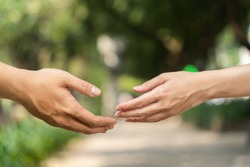 Concept of human relation, community, togetherness, teamwork, love, symbolism, culture and history. Hand of male and female reaching to each other. Nature background. Selective focus.