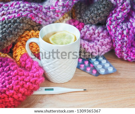 Concept of illness, colds, cure, fall and winter. Tea with lemon, thermometer, pills and a knitted blanket. #1309365367