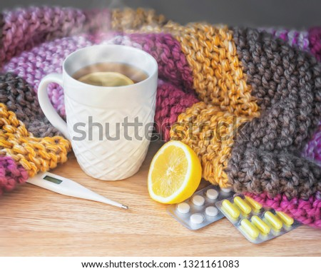 Concept of illness, colds, cure, fall and winter. Tea with lemon, thermometer, pills and a knitted blanket. #1321161083
