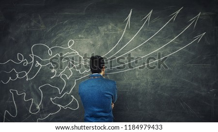 Concept of information processing as a concentrated businessman thinking in front of a huge blackboard as mesh lines come through head and transform into straight arrows as project ideas.