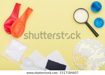 Concept of kids experiments. Flat lay magnifier glass, paint, balloon air on yellow background. Copy space.
