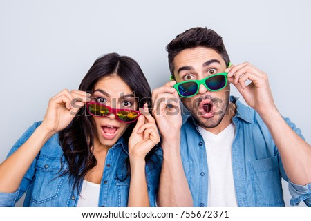 Concept of large sales and discount. Close up photo of two excited and wondered people with open mouths dressed in casual clothes, they are touching colorful glasses, isolated on grey background