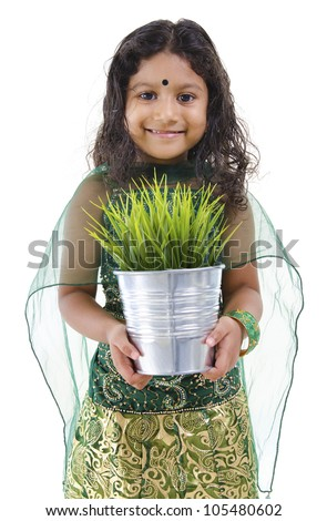 Concept of little Indian girl holding a plant on white background - stock photo