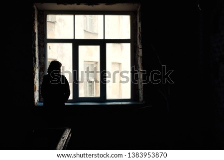 Concept of loneliness in the city, waiting and decision making. Woman looking out of the window in dark deserted house, Selective focus. Special light.	 #1383953870