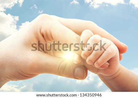 concept of love and family. hands of mother and baby on the sky