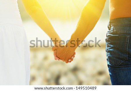 concept of love and family. the hands of lovers, men and women in beach
