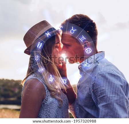 Concept of love compatibility between zodiac signs. Horoscope astrology zodiac.  Couple kissing at sunset.