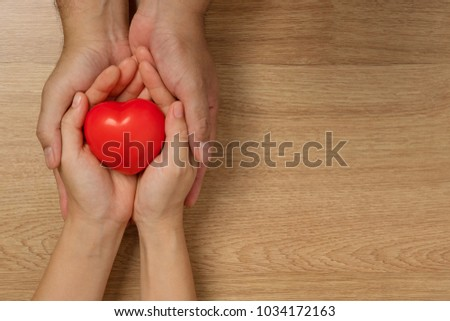 Concept of love in Valentine's Day. Hands of men and women holding red heart to give love on a wooden floor. #1034172163