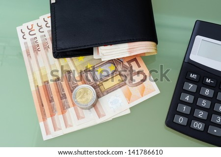 concept of making money with wallet,money,calculator on glass table