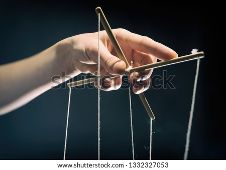 Concept of manipulation. Hand holds strings for manipulation. On dark background.