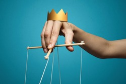 Concept of manipulation. Hand with crown holds strings for manipulation on blue background.